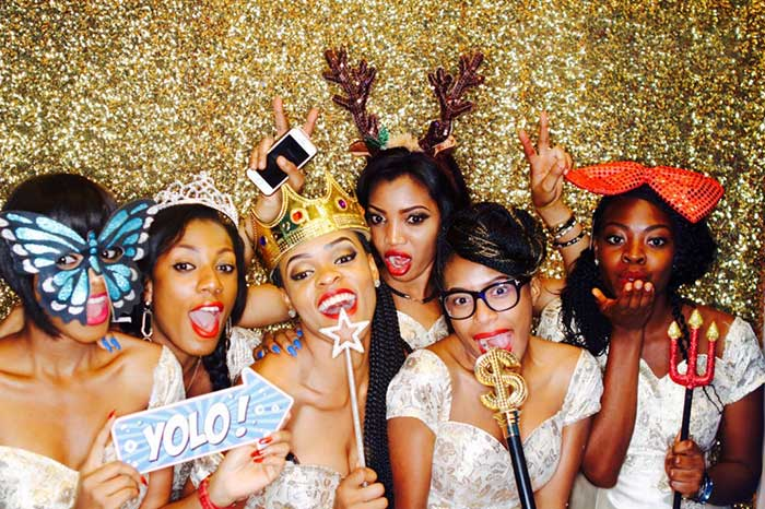 Ladies in a photo booth posing with props